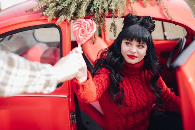 Schöne brünette frau im gestrickten pullover, der lutscher hält und aus einem roten vintage-auto herauskommt