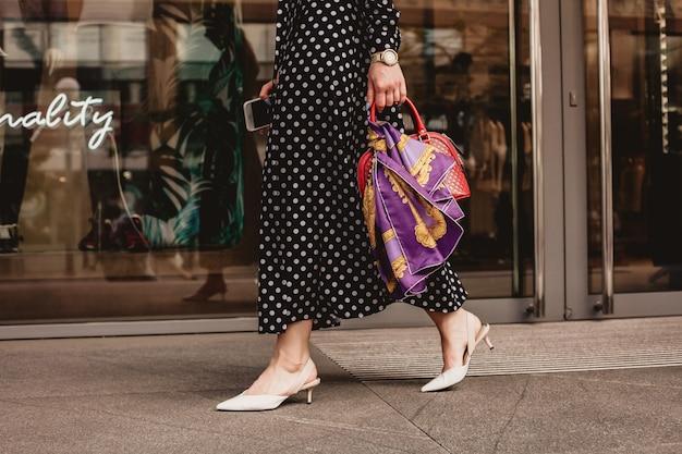 Schöne brünette frau im model-look, die ein weißes kleid mit schwarzen tupfen trägt, ist beim aufwachen auf einem stadtstraßenhintergrund mit stilvollen taschen in der hand.