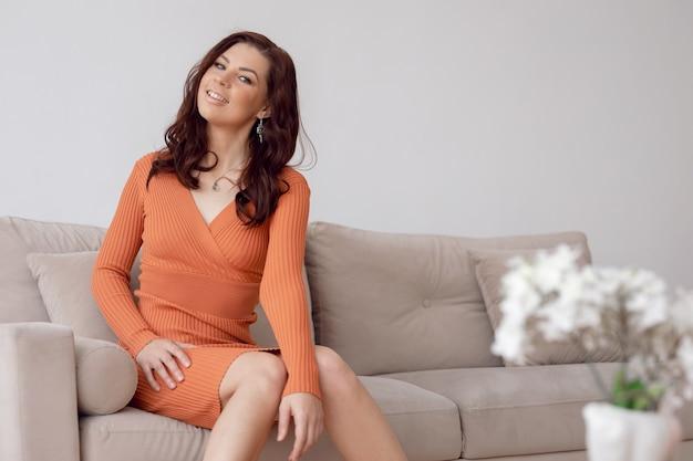 Schöne brünette frau im orange kleid sitzt auf grauem sofa