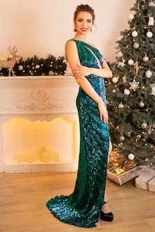 Schöne brünette frau in einem grünen kleid steht vor dem hintergrund eines weihnachtsbaumes und kamins, kerzen brennen herum.