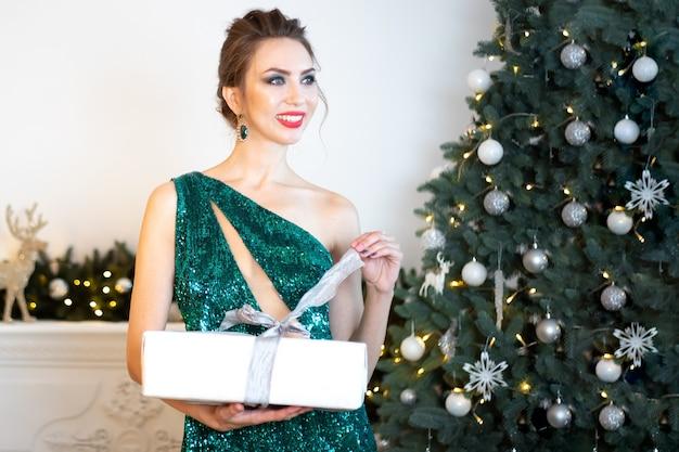 Schöne brünette frau in einem grünen kleid steht vor dem hintergrund eines weihnachtsbaums, hält eine weiße kiste mit einem geschenk in den händen und zieht das band.