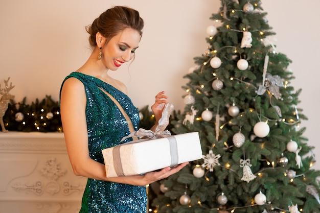 Schöne brünette frau in einem grünen kleid steht vor dem hintergrund eines weihnachtsbaums, packt ein geschenk aus, zieht das band.