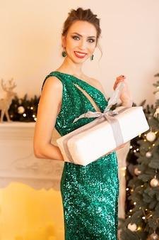 Schöne brünette frau in einem grünen kleid steht vor einem weihnachtshintergrund und hält ein weihnachtsgeschenk in ihren händen.
