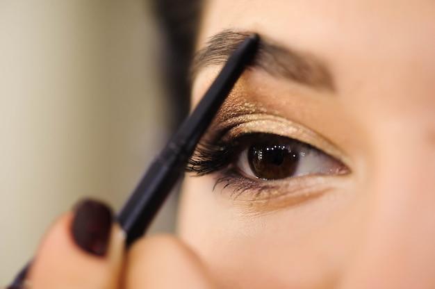 Schöne brünette frau malt die augenbrauen. schönes frauengesicht. make-up detail. schönheitsmädchen mit perfekter haut.