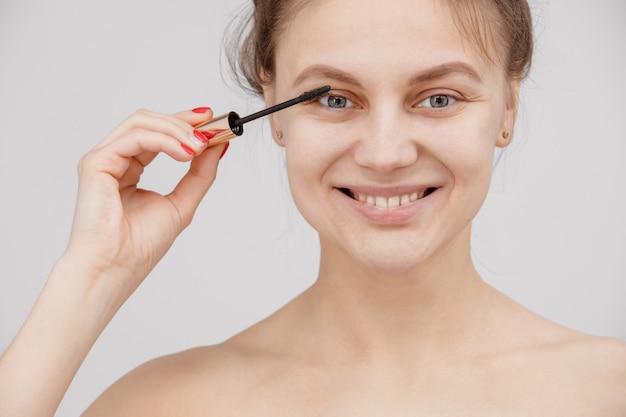 Schöne brünette frau malt die wimpern. schöne frau gesicht make-up detail. beauty mädchen mit perfekter haut