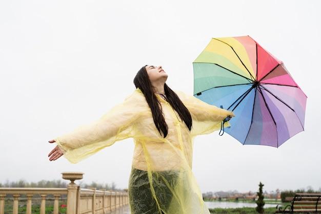 Schöne brünette frau mit buntem regenschirm, der in den regentropfen fängt und regen genießt