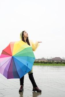 Schöne brünette frau mit buntem regenschirm im regen holding