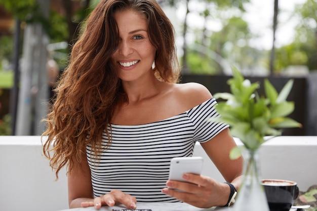 Schöne brünette frau mit fröhlichem ausdruck im terrassencafé im freien