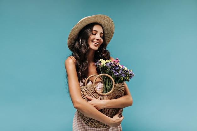 Schöne brünette frau mit gewelltem langem haar in breitkrempigem strohhut und sommerkleid mit tasche mit wildblumen an blauer wand
