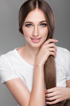 Schöne brünette frau mit glänzenden, geraden langen haaren schaut in die kamera. pflege der haare