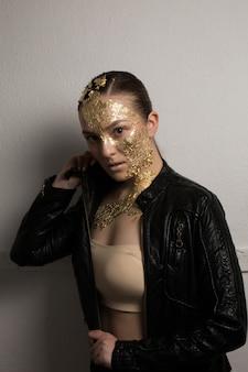 Schöne brünette frau mit kreativem make-up aus goldener folie auf gesicht, haar und hals