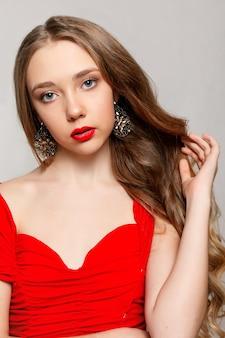 Schöne brünette frau mit langen gekräuselten haaren in einem roten kleid, das ohrringe trägt.