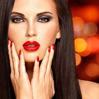 Schöne brünette frau mit roten lippen und nägeln. gesicht eines hübschen mädchens über nachtlichterhintergrund