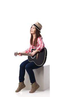 Schöne brünette frau sitzt auf würfel und spielt ihre gitarre. gitarre spielen