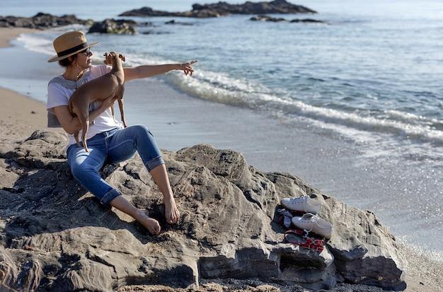 Schöne brünette frau spielt mit hund am strand
