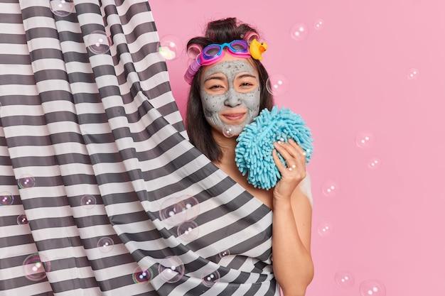 Schöne brünette frau trägt tonmaske auf gesicht fühlt sich erfrischt hält bad schwamm wendet tonmaske für hautverjüngung posen hinter duschvorhang isoliert über rosa hintergrund mit blasen