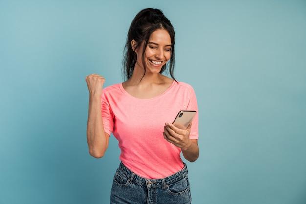 Schöne brünette freut sich über den sieg, sie hält ein telefon