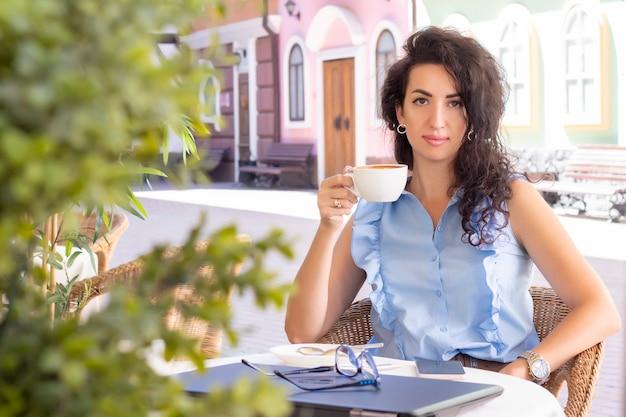 Schöne brünette glückliche geschäftsfrau, die kaffee in einem café auf der straße trinkt