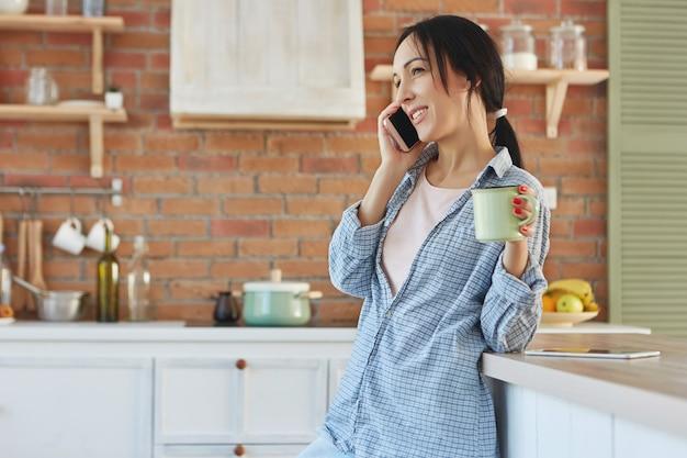 Schöne brünette hausfrau fühlt sich zu hause gelangweilt, plaudert lange über smartphone