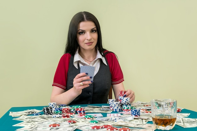 Schöne brünette im kasino, das spielkarten hält