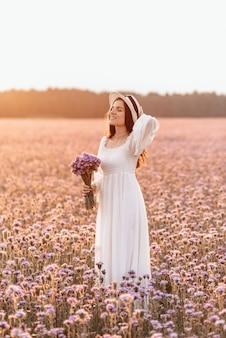 Schöne brünette in einem lavendelfeld bei sonnenuntergang erstaunliches porträt