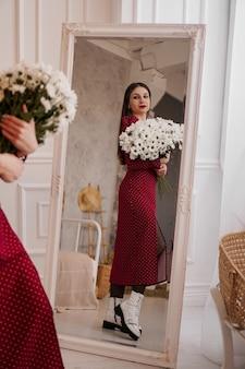 Schöne brünette in einem roten kleid mit einem strauß gänseblümchen sieht zu hause im spiegel aus. frühlingsfoto. foto in voller länge