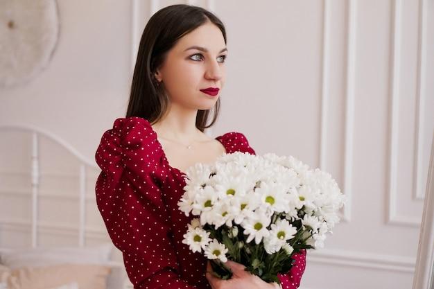 Schöne brünette in einem roten kleid mit einem strauß gänseblümchen zu hause