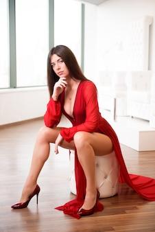 Schöne brünette in einem weißen studio in einem roten kleid.