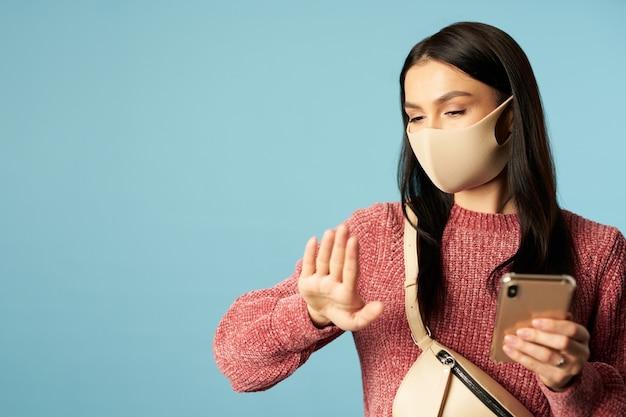 Schöne brünette in einer schützenden gesichtsmaske, die ihre finger im studio betrachtet