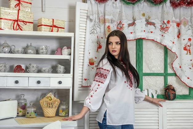 Schöne brünette in traditioneller ukrainischer bluse posiert im studio