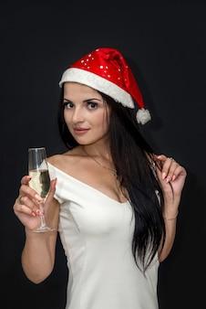 Schöne brünette in weihnachtsmütze und champagner lokalisiert auf schwarz