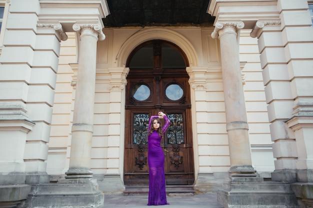 Schöne brünette junge frau, die modische kleidung trägt, wundervolles haar, das in der stadt aufwirft. modefoto