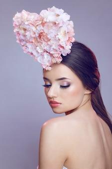 Schöne brünette junge frau mit kreativem make-up und herzförmigen geformten blumen auf kopf