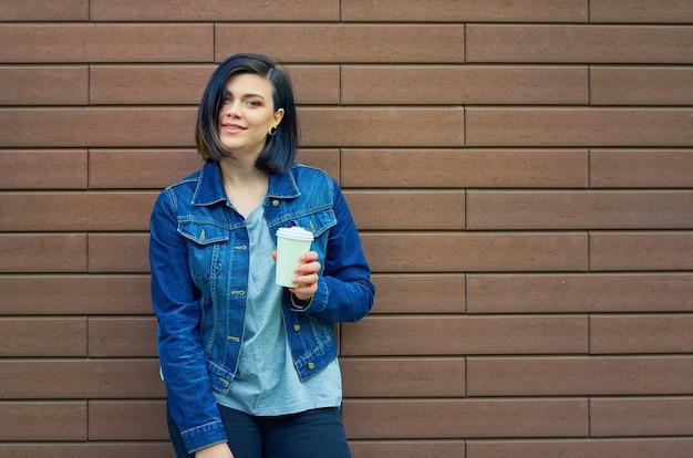 Schöne brünette junge frau mit tunneln in den ohren in einer blauen jeansjacke mit einer tasse kaffee, die vor ziegelmauer steht.