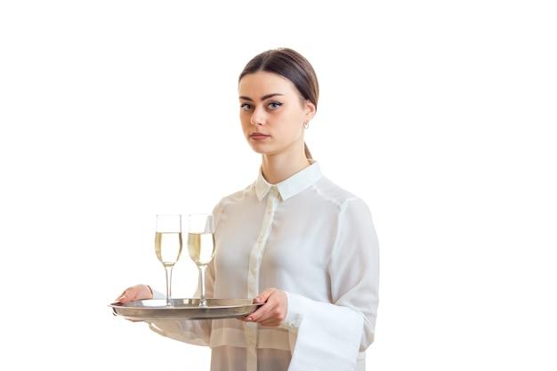Schöne brünette kellnerin in uniform mit einem trey mit wein isoliert auf weißem hintergrund