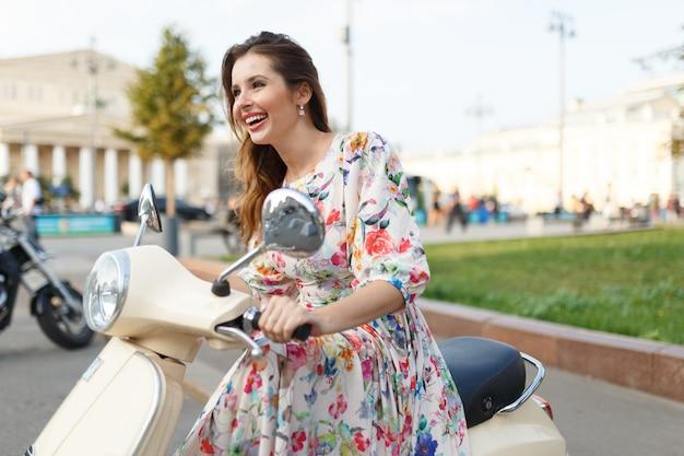 Schöne brünette lächelnd beim sitzen auf einem motorrad