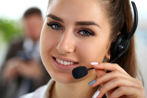 Schöne brünette lächelnde callcenter-angestellte bei der arbeit