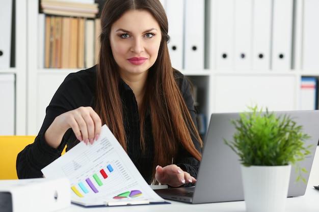 Schöne brünette lächelnde geschäftsfrau arbeiten mit laptop