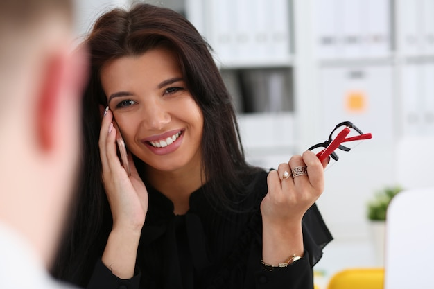 Schöne brünette lächelnde geschäftsfrau sprechen handy