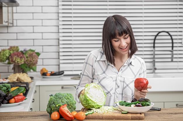 Schöne brünette lächelt und schneidet gemüse auf einem salat auf dem hintergrund eines modernen kücheninnenraums.