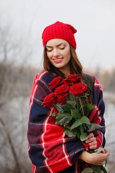 Schöne brünette mit einem strauß roter rosen in ihren händen