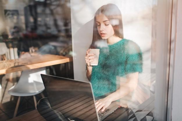 Schöne brünette mit laptop im café. junge attraktive frau macht pläne für die zukunft und sitzt vor einem offenen laptop in einem gemütlichen café