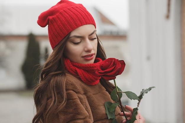 Schöne brünette mit roter rose in ihren händen