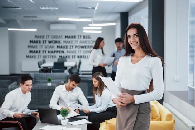 Schöne brünette. porträt des jungen mädchens steht im büro mit angestellten im hintergrund