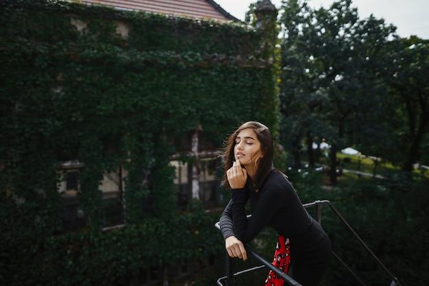 Schöne brünette posiert auf einem schwarzen treppenhaus