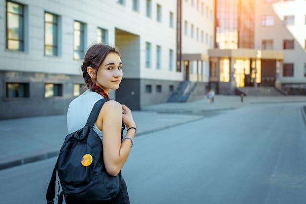 Schöne brünette von hinten mit einem schwarzen rucksack hinter dem college.