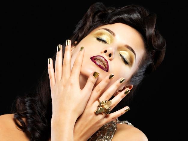 Schöne brunetfrau mit goldenen nägeln und art make-up der augen - auf schwarzem hintergrund