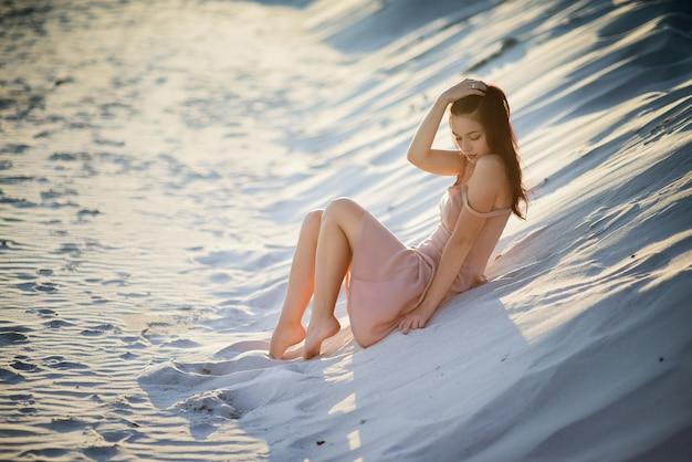 Schöne brunettedame steht auf weißem sand in den strahlen der sonne still