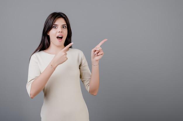 Schöne brunettefrau aufgeregt und überrascht, auf das copyspace zeigend lokalisiert über grau
