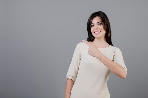 Schöne brunettefrau, die auf das copyspace lokalisiert über grau lächelt und zeigt